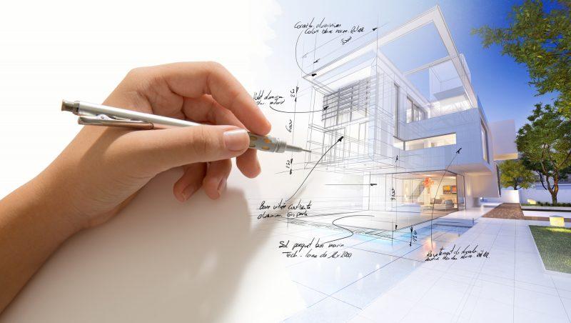 Mano con bolígrafo escribiendo anotaciones sobre imagen y plano edificio