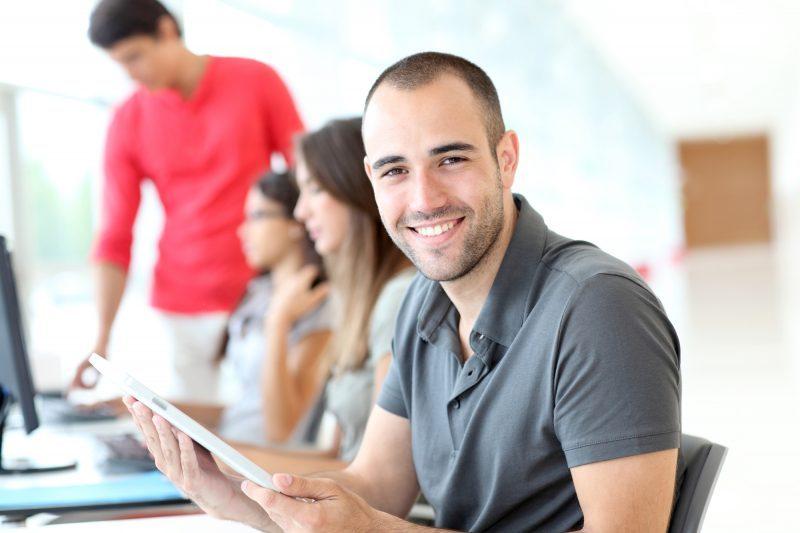 Imagen alumnos, al fondo de pie con camiseta roja, dos chicas sentadas y un chico con camiseta gris