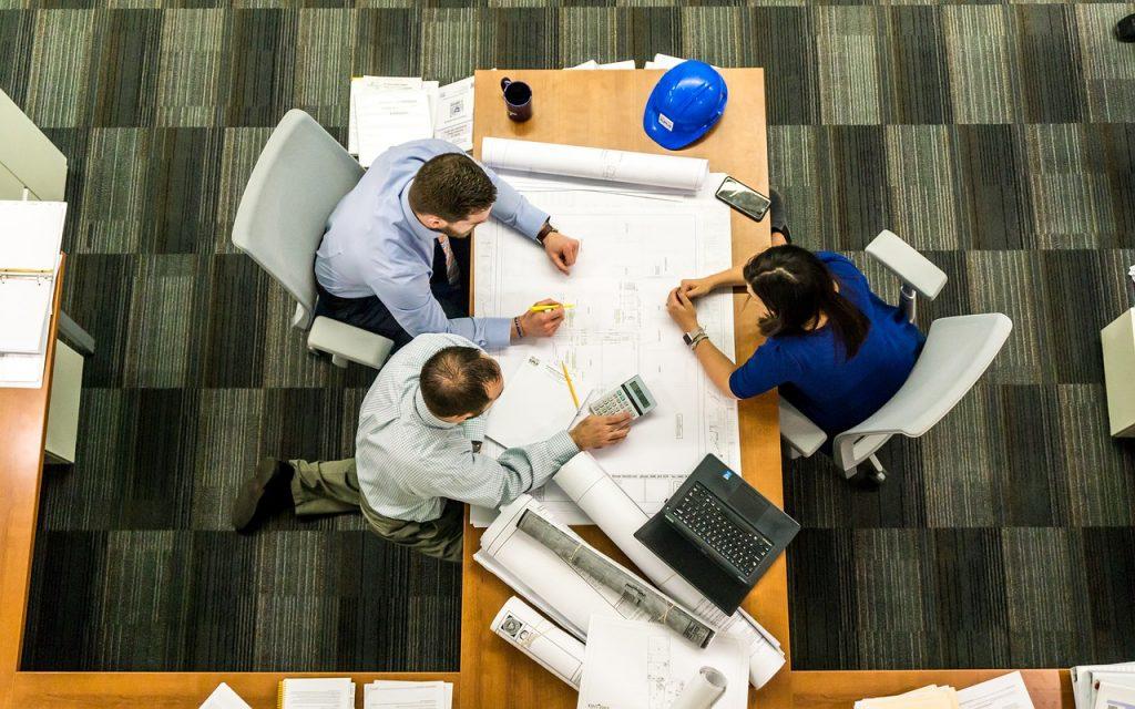 alumnos cursos arquitectura sevilla trabajando sobre una mesa con, calculadora, ordenador, planos...